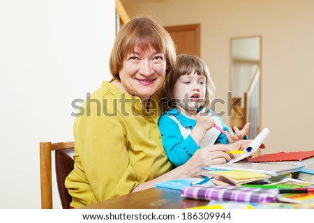 Happy grandmother plays with baby  in home interior
