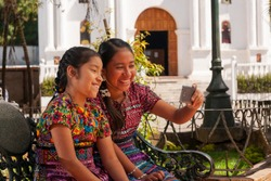 Happy indigenous girls taking selfie with smart phone in a park of Guatemala.