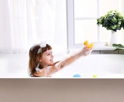 Happy little baby girl sitting in bath tub  in the bathroom with little ducks. Portrait of baby bathing in a bath full of foam near window