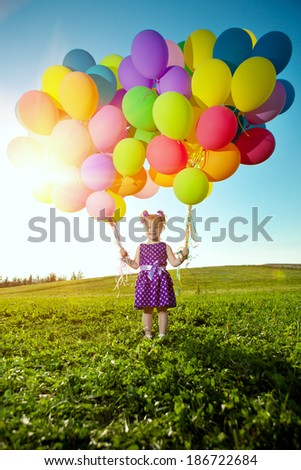 Happy little girl holding colorful balloons. Child playing on  green meadow. Smiling  kid. Portrait of baby outdoor