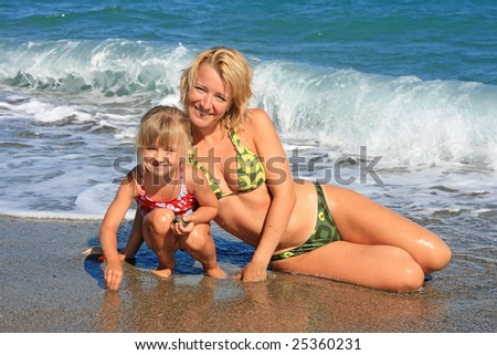 Happy mum with a daughter have a rest on the sea