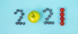 2021 Happy New Year and New You with fruit and vegetable; Blueberries, green apple and Tomato on blue background. Goals, Healthy, Resolution, Time to New Start and dieting concept