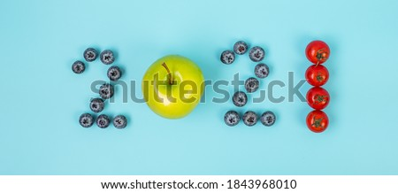 2021 Happy New Year and New You with fruit and vegetable; Blueberries, green apple and Tomato on blue background. Goals, Healthy, Resolution, Time to New Start and dieting concept ストックフォト ©