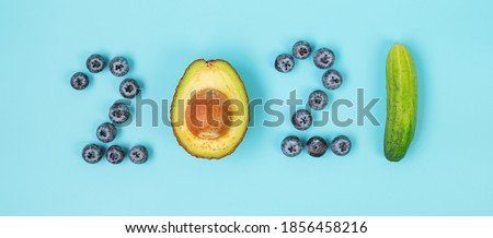 2021 Happy New Year and New You with fruits and Vegetables; Blueberries, Avocado and cucumber on blue background. Goals, Healthy, Resolution, Time to New Start and dieting concept ストックフォト ©