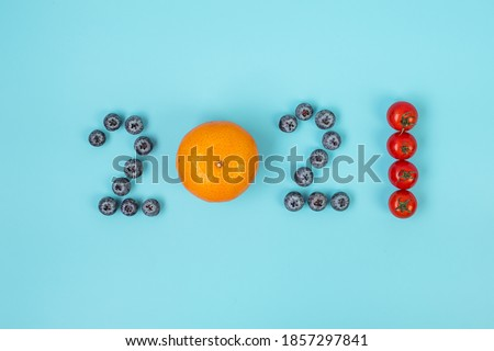 2021 Happy New Year and New You with fruits and Vegetables; Blueberries, Orange and Tomato on blue background. Goals, Healthy, Resolution, Time to New Start and dieting concept ストックフォト ©