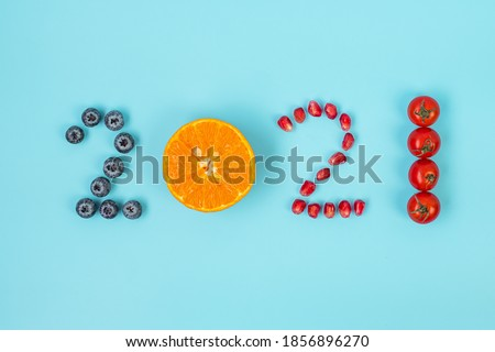 2021 Happy New Year and New You with fruits and Vegetables; Blueberries, Orange, Pomegranate seeds and Tomato on blue background. Goals, Healthy, Resolution, Time to New Start and dieting concept ストックフォト ©