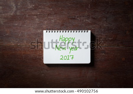 happy new year 2017 is written on small opened notepad with blank area for