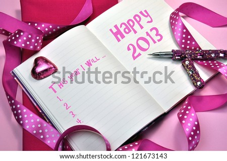 2013 Happy New Year message in diary with New Year Resolutions list on pink background with ribbons and pink writing pen.