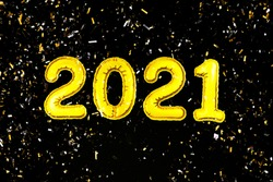 2021 Happy New Year numbers text. Golden metallic foil balloons and confetti on black background flat lay. Christmas party holiday greeting decor. Banner, postcard template. Wallpaper clipart