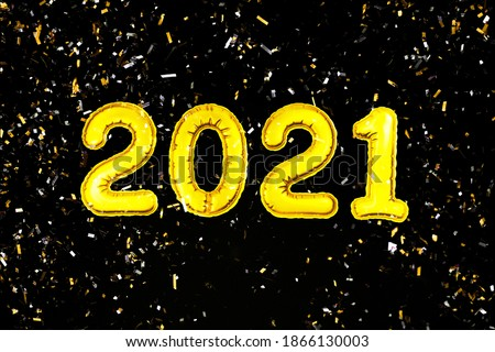 Photo of  2021 Happy New Year numbers text. Golden metallic foil balloons and confetti on black background flat lay. Christmas party holiday greeting decor. Banner, postcard template. Wallpaper clipart
