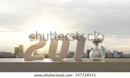 2018 happy new year. Resolutions, goals, start up, refresh concept. Wood numbers and hourglass clock on wooden tabletop on panoramic skyline and buildings in the morning background.