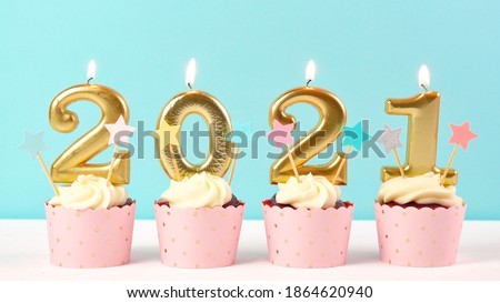 2021 Happy New Year's Eve pastel pink and blue theme cupcakes with large gold candles.