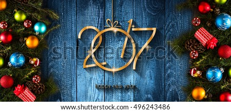 2017 Happy New Year seasonal background with real wood green pine, colorful Christmas baubles, gift boxe and other seasonal stuff over an old wooden aged background #496243486