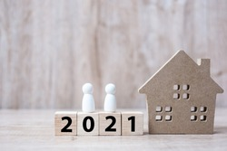 2021 Happy New Year with house model and people  on wooden background. Banking, real estate, investment, financial, savings and New Year Resolution concepts