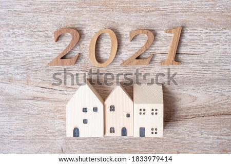 2021 Happy New Year with house model on table wooden background. Banking, real estate, investment, financial, savings and New Year Resolution concepts