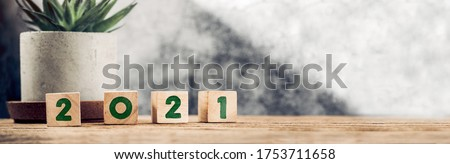 2021 happy new year wood number (3d rendering) on wood table background with sunlight window create leaf shadow on wall with blur green plant foreground.panoramic banner mockup for display product Foto stock ©