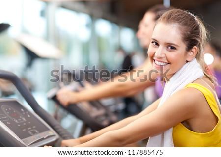 Happy people doing indoor biking in a fitness club