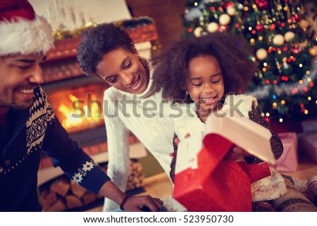 Happy smiling African American family in Christmas atmosphere opening Christmas present #523950730
