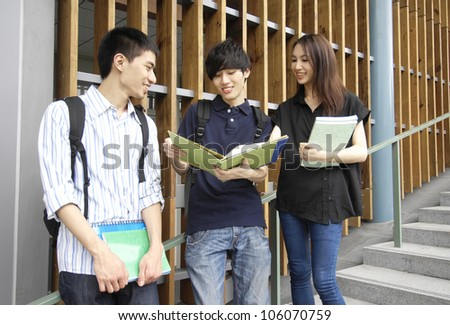 Happy smiling students standing together with books at a campus
