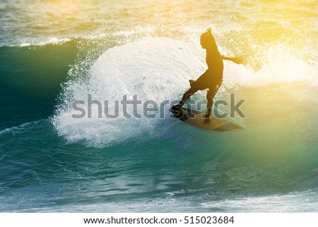 Happy surfer enjoy big wave and foam at tropical beach sunset. Surfing silhouette.