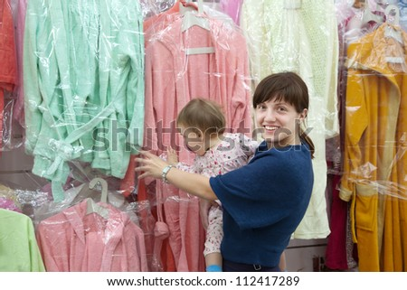 Happy woman and child chooses bathrobe at shop