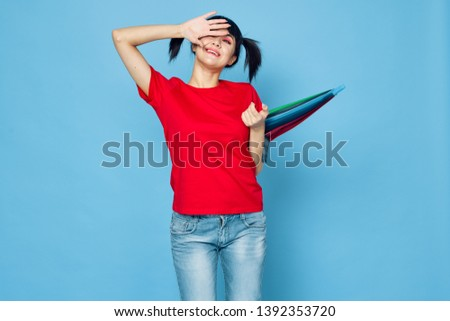 happy woman covering her face with her hands holding a colored umbrella on a blue background                             #1392353720