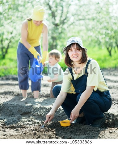 Happy women with child works at garden in spring