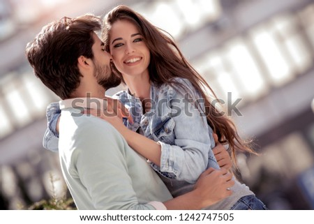 Happy young loving couple standing outdoors together and enjoy together.