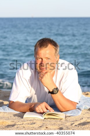 Happy young man reading on the shore