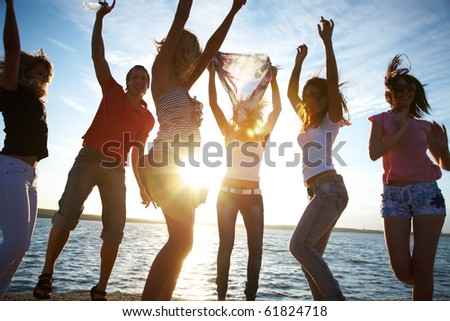 happy young people are  dancing at the beach on  beautiful summer sunset