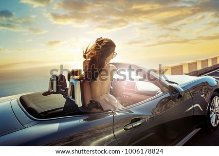 happy young woman enjoying a ride in a convertible car  #1006178824