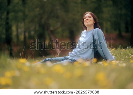 Happy Young Woman Sitting in the Grass Enjoining Nature. Carefree person resting in a countryside field experiencing mindfulness and calmness   Stok fotoğraf ©