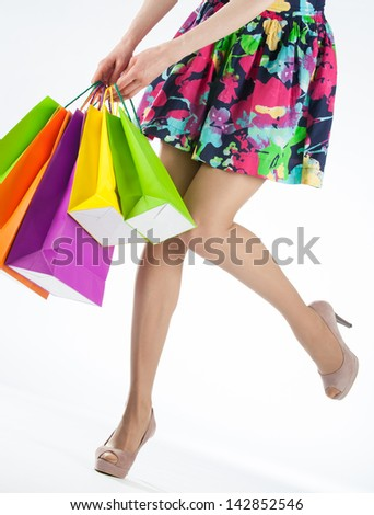 Happy young woman with multicolored shopping bags, closeup shot of female legs on white background