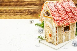 Сharcuterie chalet or The Meat Hut as Christmas newest food trend. New Year Keto gingerbread house with traditional decor and symbols. White putty background, copy space