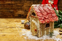 Сharcuterie chalet or The Meat Hut as Christmas newest food trend. New Year Keto gingerbread house with traditional decor and symbols. Festive wooden boards background, copy space