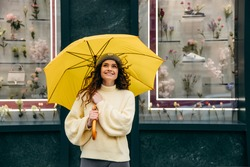 Сharming young curly  woman use yellow umbrella at the street of megapolis city in rainy day