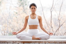 Ð¡harming young woman sitting in lotus pose and meditating with closed eyes during yoga classes on the windowsill in the gym