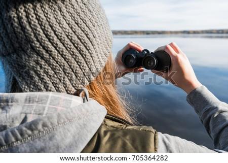 ?he blonde girl is looking through binoculars Zdjęcia stock ©