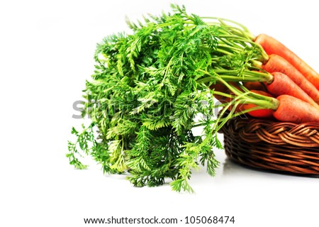 heap of fresh carrots with leaves  in  basket