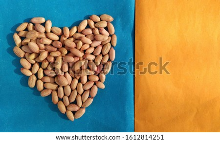 Heart made of groundnuts on a colorful background