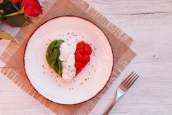 Heart shaped Italian Caprese Salad arranged by Italian basil,buffalo mozzarella and tomatoes look like Italian Flag on plate with white wood table background.Love Italian food concept for Valentine