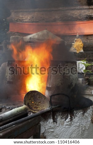 Heat in ancient metal crucible , Ancient metal cast for buddha statue  in Lok Molee Temple, Chiangmai, Thailand.