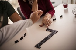 Helping hand. Senior people playing dominoes  at home. Focus is on hands.