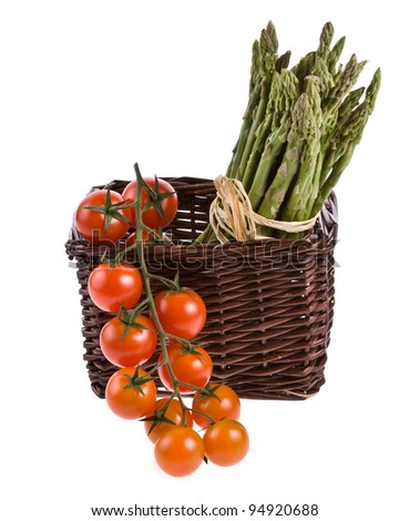?herry tomatoes and green asparagus in a small basket