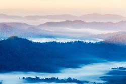 High angle view over tropical mountains layer with white fog in early morning in Thailand.