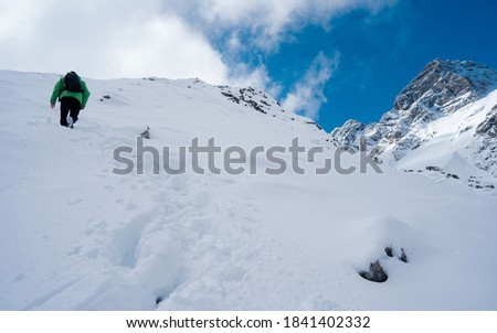 Hiker ascent to the summit. Winter ice and snow climbing in mountains. A success of mountaineer reaching the summit. Outdoor adventure sports in winter alpine moutain landscape.
