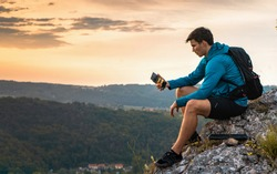 Hiker in blue sit alone on the rock summit. Wonderful daybreak in mountains, rear view of backpacker sit on edge. Man sit on the rock. Amazing view from summit
