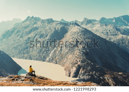 Hiker watching to Sun at horizon. Beautiful moment the miracle of nature. Colorful mist in valley. Man hike. Mountain Pass in Switzerland. Autumn mood at sunset. #1221998293