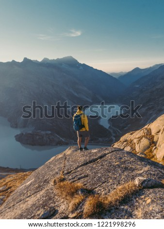 Hiker watching to Sun at horizon. Beautiful moment the miracle of nature. Colorful mist in valley. Man hike. Mountain Pass in Switzerland. Autumn mood at sunset. #1221998296