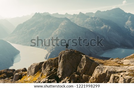 Hiker watching to Sun at horizon. Beautiful moment the miracle of nature. Colorful mist in valley. Man hike. Mountain Pass in Switzerland. Autumn mood at sunset. #1221998299